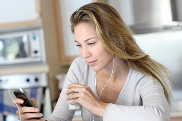 Young woman using smartphone at home with earphones