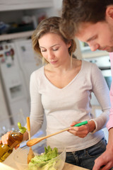 Couple enjoying preparing dinner in kitchen