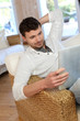 Portrait of young man relaxing in sofa with electronic tablet