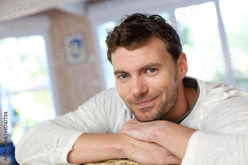 Portrait of young smiling man relaxing in sofa