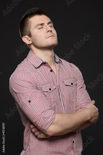 Business man standing with folded hands with eyes closed