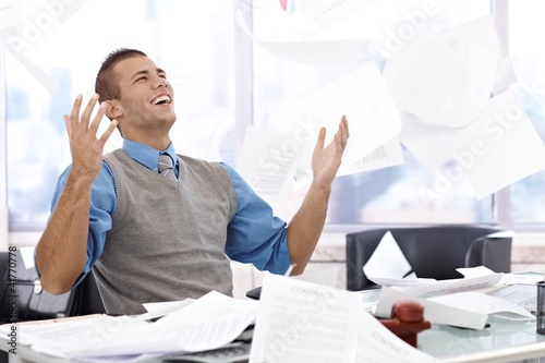 Happy businessman throwing documents