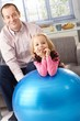 Portrait of father and daughter with fit ball