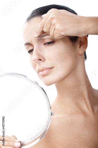 Young female examining wrinkles in mirror