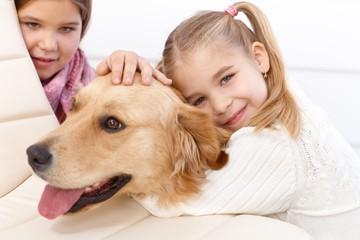 Little girl hugging pet dog smiling