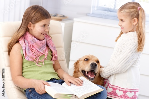 Little sisters with pet dog at home