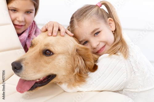 Little girl hugging pet dog smiling