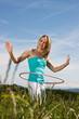Blonde Frau übt mit rosa Hula Hoop Reifen