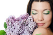 Beautiful woman with spring flowers of a lilac. Skincare