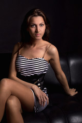 Девушка в студии на кожаном диване