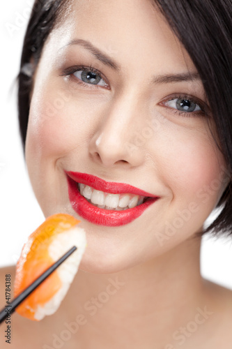 Young woman holding sushi with a chopsticks, closeup