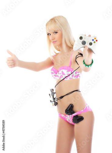 Young blonde woman in pink lingerie posing with game joysticks