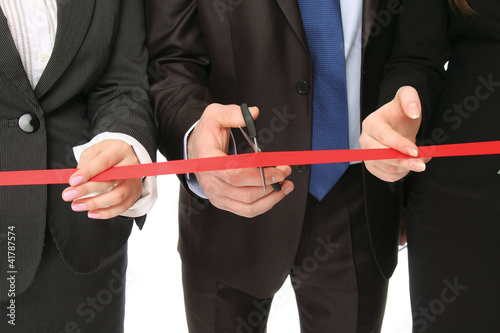 Business people cutting a red ribbon with a pair
