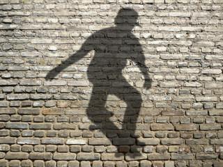 ombre de skate-boarder sur mur en briques