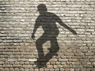 ombre de skateboarder sur mur de briques