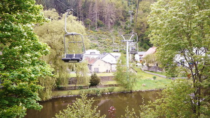 Chair lift crossing trees and water