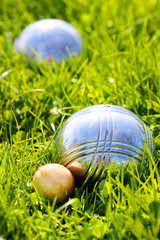 The bocce balls on a green grass.