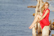 young beautiful woman sitting on old wooden bridge