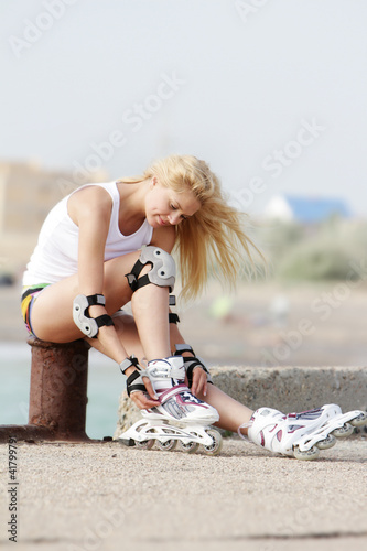 young smiling woman getting ready for rollerblading / roller ska