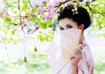 Asian style portrait of young woman with fan in the garden