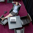 Young business woman with laptop resting on chair