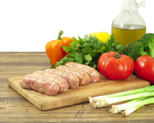 Raw sausages and fresh vegetables on a cutting board
