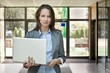 Young business woman with laptop in office