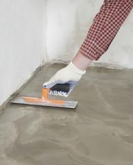 Construction worker spreading wet concrete