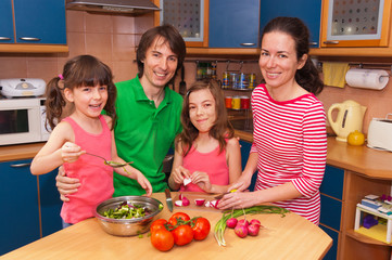 Family cooking at home. Happy parents with kids cook salad