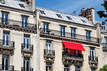Balcon au store rouge sur une façade de pierre.