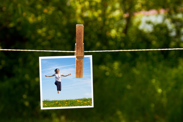 photograph of jumping happy girl with clothespeg