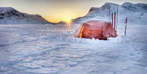 Zelt und Sonnenaufgang auf Winter - Trekkingtour
