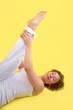 Frau beim Yoga mit gelbem Hintergrund