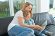 Mutter kuschelt mit Sohn auf dem Fofa und liest vor