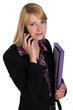 Office worker carrying a file folder while talking on the phone