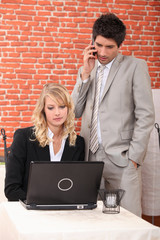Businessman and assistant watching laptop