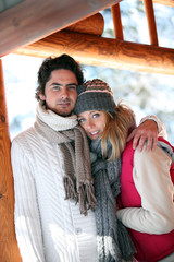 Couple stood hugging on chalet patio