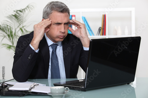 Man stressed with a laptop