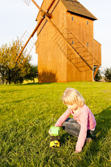 playing little girl at wooden windmill, Stary Poddvorov, Czech R