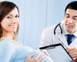 Doctor and pregnant woman with prescription at office