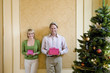 Mature couple by Christmas tree holding pink gift boxes, smiling, portrait