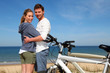 Couple standing by the ocean with bicycles