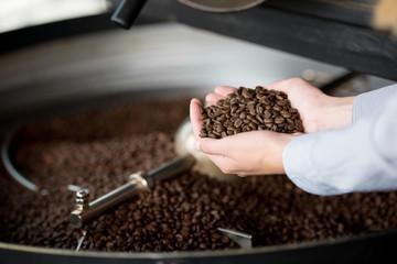 frau in der rösterei hält kaffeebohnen in der hand