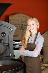 lächelnde frau steht in der kaffeerösterei