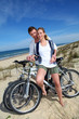 Cheerful couple biking on a sand dune