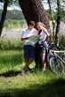 Couple on a bike ride making a stop to look at map