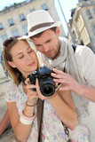 Couple enjoying taking pictures while visiting city