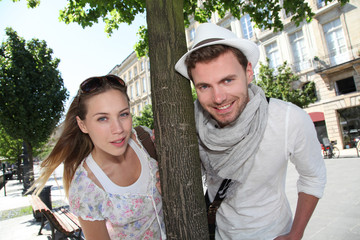 Couple standing by a tree in town