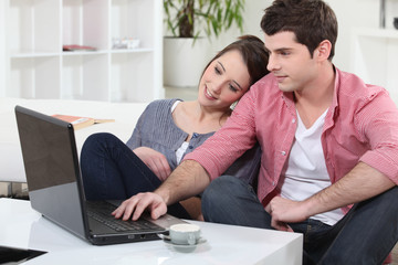 Couple relaxing at home in front of their laptop