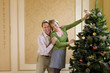Couple indoors putting angel on top of Christmas tree, smiling, portrait.